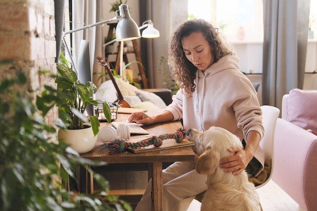 犬が彼女と遊びたいと思っている間、自宅のコンピューターでテーブルで働いている若い女性