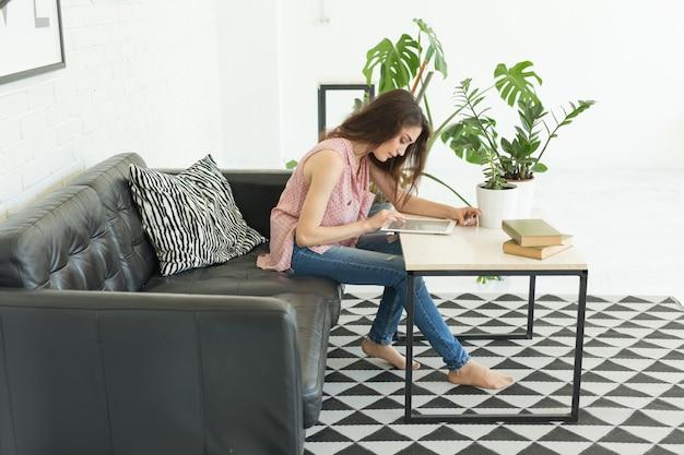 거실에서 태블릿에 의해 작업하는 젊은 여자