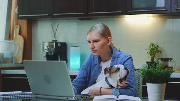 Young woman working on the computer and holding small dog on her hands