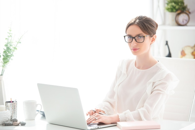 Young woman working at a desk with a laptop in an office.