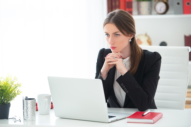 Young woman working at a desk with a laptop in an office