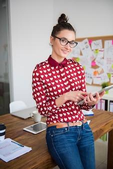 Giovane donna che lavora sulla tavoletta digitale in ufficio