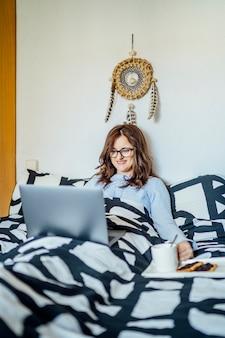 컴퓨터와 집에서 침대에서 일하는 젊은 여자.