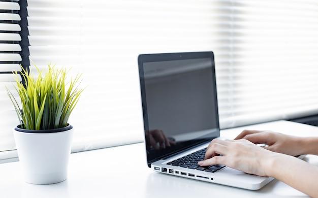 Молодая женщина работает из дома на компьютере.
