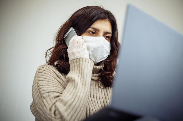 コロナウイルスパンデミックによる検疫中に在宅勤務の若い女性。美しい少女は、医療用マスクと手袋を着用し、ラップトップで入力し、電話でビジネスについて話し合って家にいます。