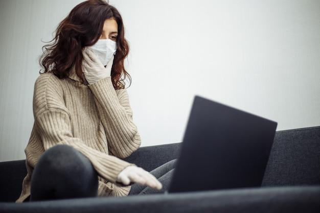 コロナウイルスパンデミックによる検疫中に在宅勤務の若い女性。美しい少女は、医療用マスクと手袋を着用し、ラップトップで入力して家にいます。 covid-19エピデミックの世界的な概念。