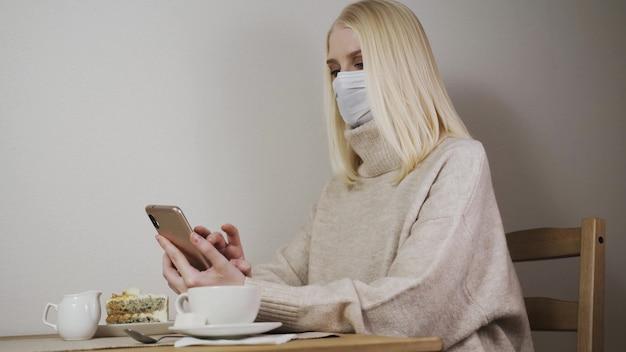 코로나 바이러스 예방을위한 보호 마스크를 쓰고 재택에서 일하는 젊은 여성-코로나 19 예방 격리에서 휴대 전화를 사용하는 비즈니스 소녀-유행성 바이러스 위기 동안 스마트 한 일