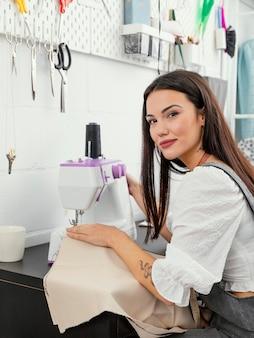 Giovane donna che lavora nel suo laboratorio di fashion design
