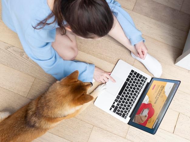 Giovane donna che lavora al suo computer portatile accanto al suo cane