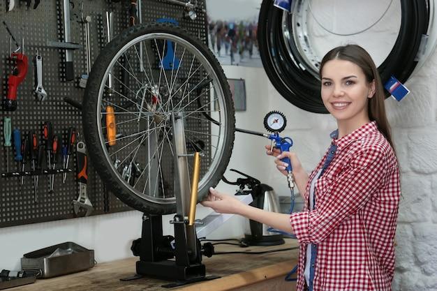 自転車修理店で働く若い女性