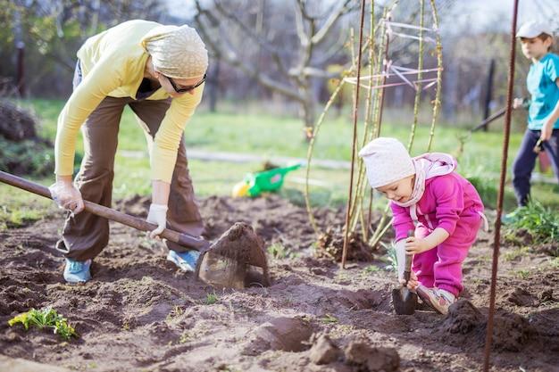 그녀의 어린 딸이 그녀와 아들 옆에 삽을 가지고 노는 동안 정원에서 일하는 젊은 여자