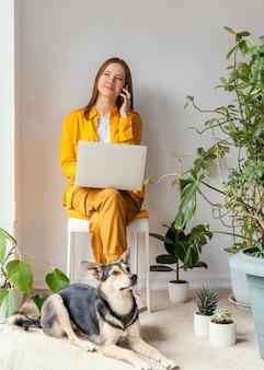 그녀의 강아지 옆에있는 그녀의 집 정원에서 일하는 젊은 여자