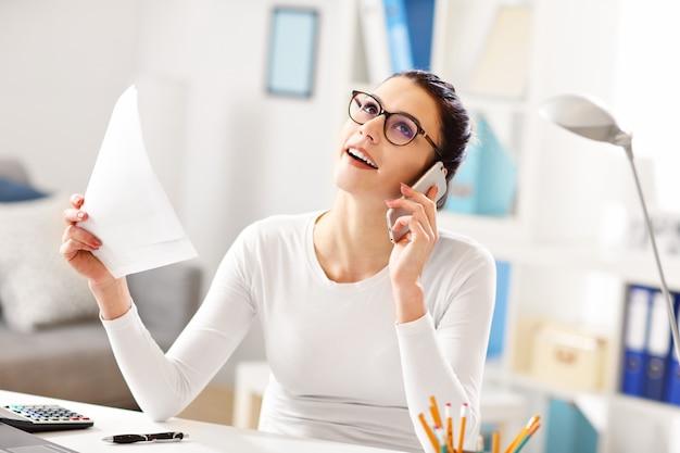 Молодая женщина работает в своем домашнем офисе