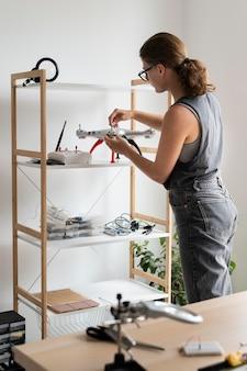創造的な発明のために彼女のワークショップで働いている若い女性