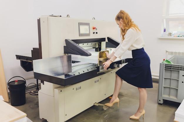 Молодая женщина, работающая на полиграфической фабрике. печатный станок.