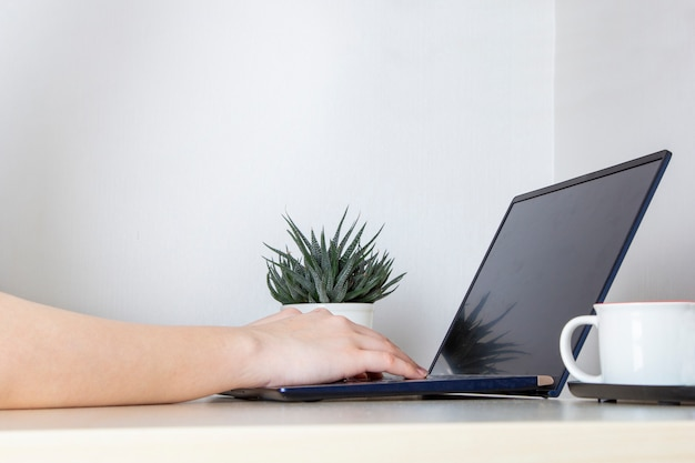 Young woman working for laptop from home on white desk.