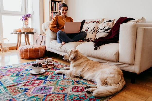 Young woman working on laptop at home. cute golden retriever dog besides.