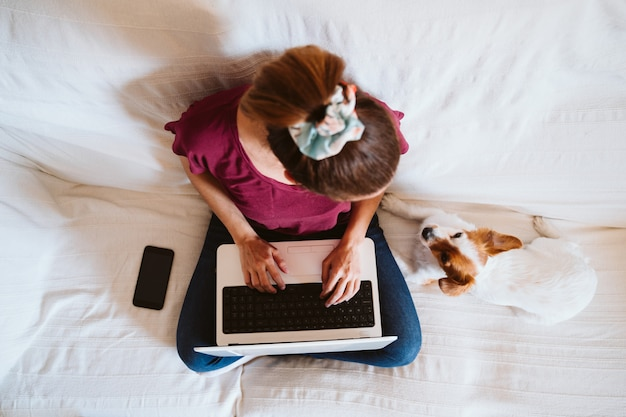 Young woman working on laptop at home, sitting on the couch, cute small dog besides. technology and pets concept