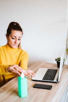 Young woman working on laptop at home, using hand sanitizer alcohol gel. stay home during coronavirus covid-2019 concept