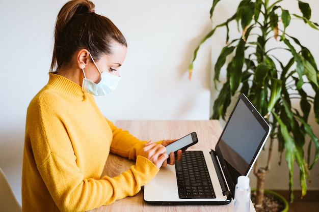 Young woman working on laptop at home, wearing protective mask. work from home, stay safe during coronavirus covid-2019 concpt
