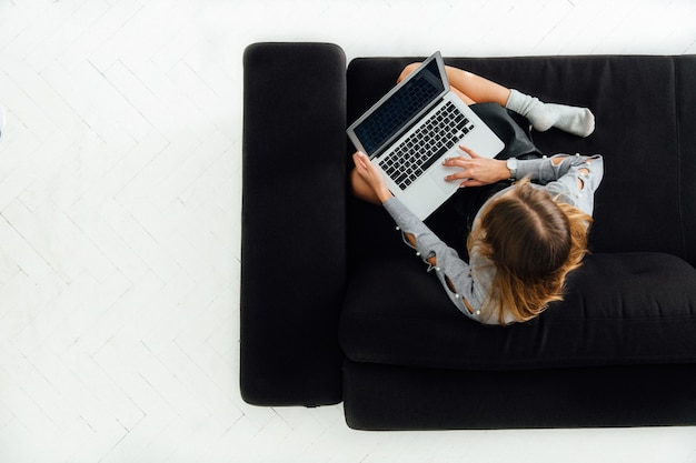 Young woman working on laptop, sitting on black cozy sofa, white floor.