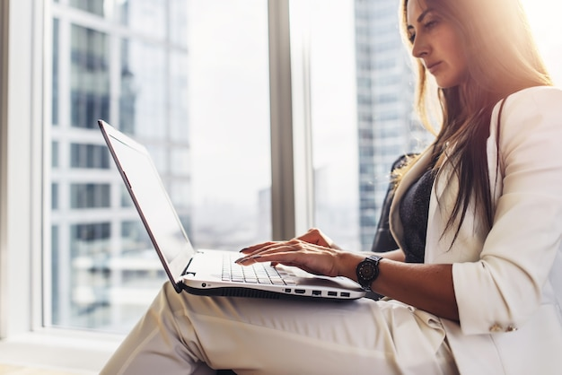 Young woman working on laptop sitting at home.