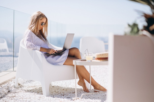 Young woman working on laptop on a vacation