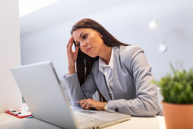 Young woman working at office desk in front of laptop suffering from chronic daily headaches