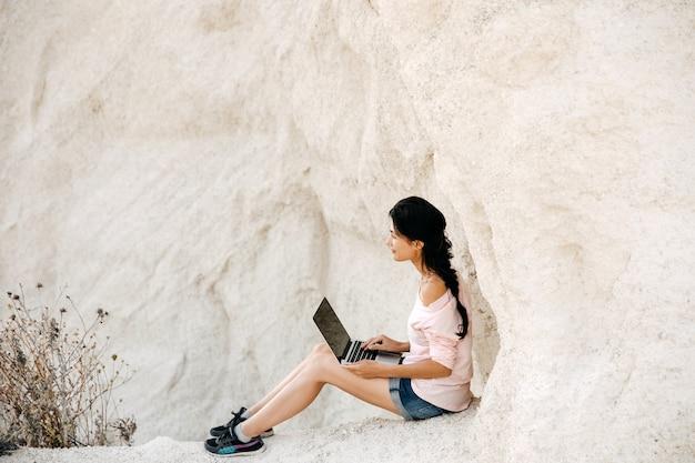 ビーチの崖でラップトップに取り組んでいる若い女性。フリーランスのコンセプト。