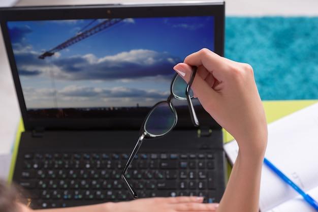 인터넷 서핑을 하는 동안 안경을 손에 들고 랩톱 컴퓨터에서 작업하는 젊은 여성, 손과 랩톱 화면을 닫습니다.