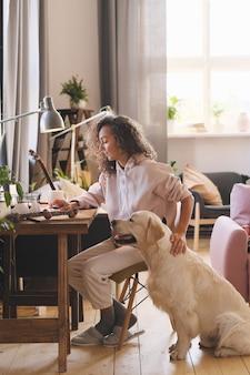 彼女の犬が彼女の近くに座っている間、自宅のテーブルでコンピューターで作業している若い女性