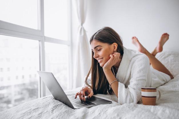 Молодая женщина работает на компьютере в постели