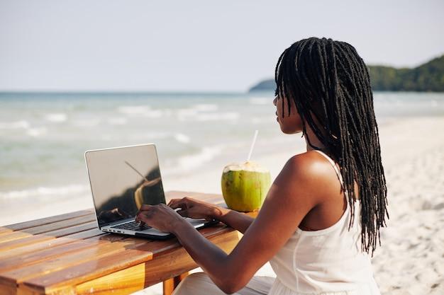 해변에 컴퓨터에서 작업하는 젊은 여자