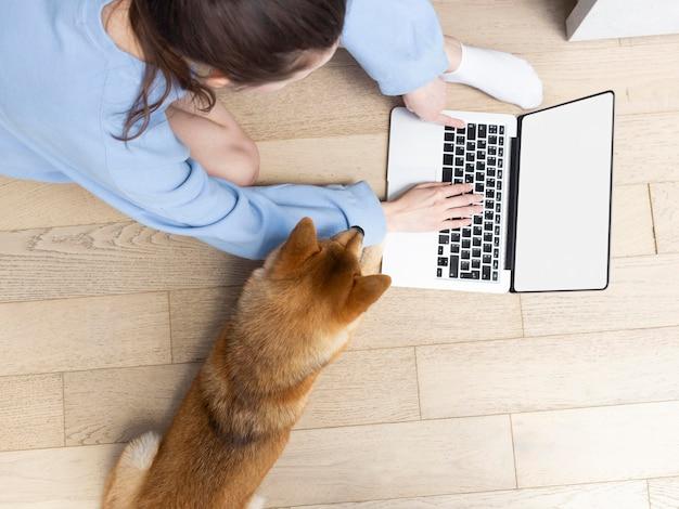 犬の横でラップトップで作業する若い女性