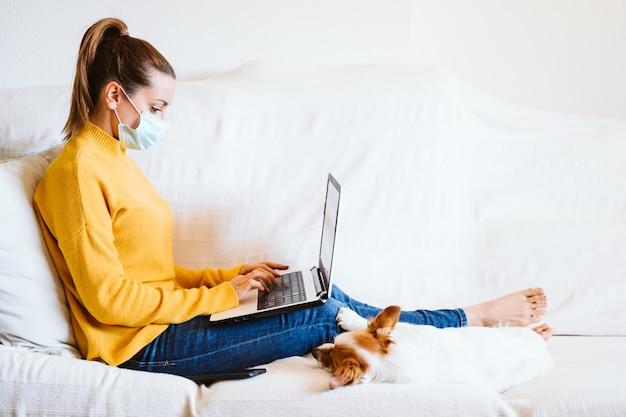 Молодая женщина работает на ноутбуке дома, сидя на диване, носить защитную маску. к тому же милая маленькая собачка. пребывание дома концепции во время коронавируса covid-2019