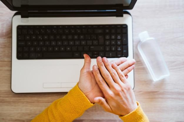 手の消毒剤アルコールゲルを使用して、自宅のラップトップに取り組んでいる若い女性。コロナウイルスcovid-2019コンセプトの最中に家にいる