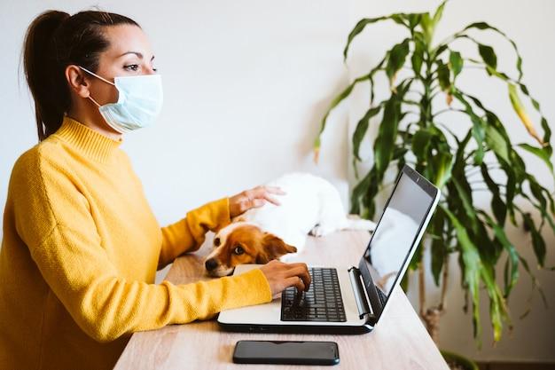 젊은 여자 집에서 노트북에 작업 보호 마스크, 귀여운 작은 개 외 입고. 코로나 바이러스 covid-2019 concpt 동안 집에서 일하고, 안전을 유지하십시오