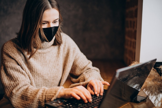 Молодая женщина, работающая на ноутбуке в кафе в маске