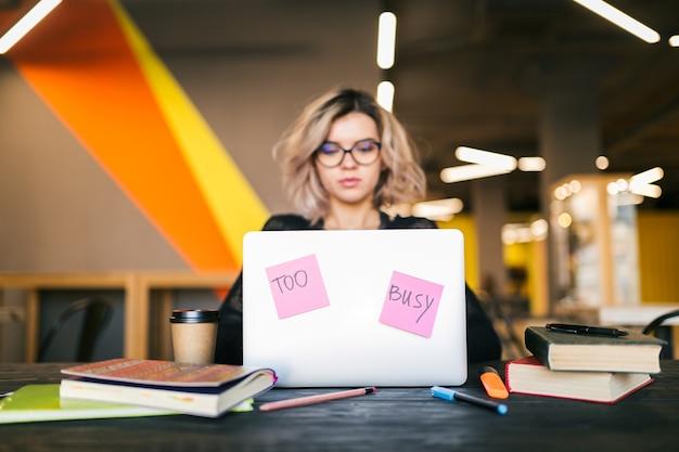 コワーキングオフィスでラップトップに取り組んでいる若い女性
