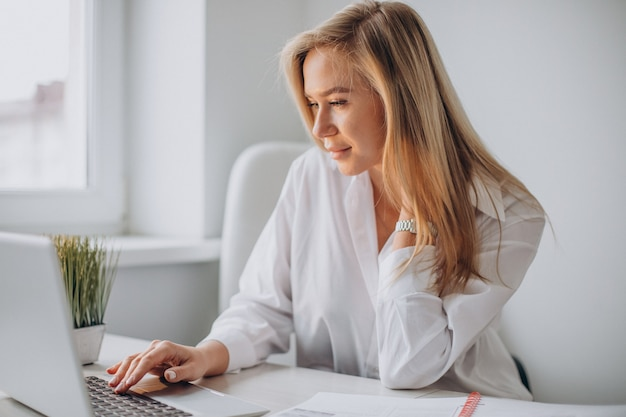 Молодая женщина работает на ноутбуке в офисе и смотрит в камеру