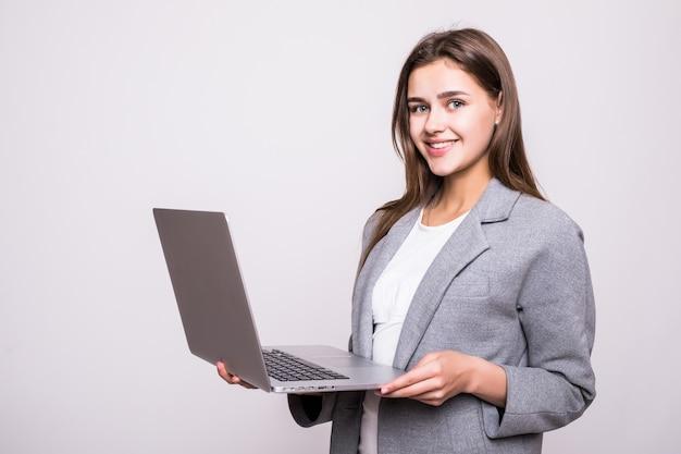 Молодая женщина работает на ноутбуке на белом фоне