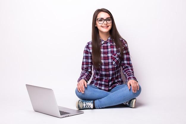 흰색 배경 위에 바닥에 노트북에서 일하는 젊은 여자