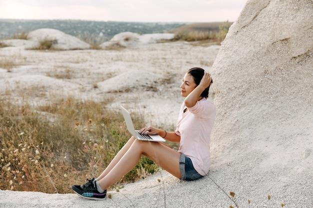 キャニオンで、屋外のラップトップに取り組んでいる若い女性。フリーランスのコンセプト。