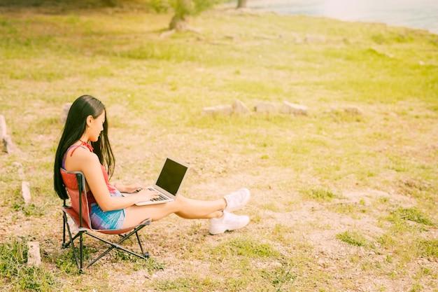 야외에서 노트북에서 일하는 젊은 여자