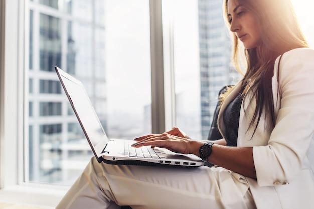 Молодая женщина, работающая на ноутбуке, сидя у себя дома.