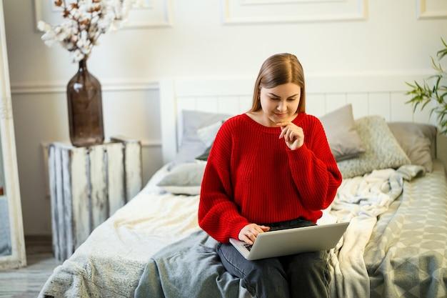 Молодая женщина, работающая на ноутбуке, сидя на кровати у себя дома. работа из дома во время карантина. девушка в свитере и джинсах дома на кровати