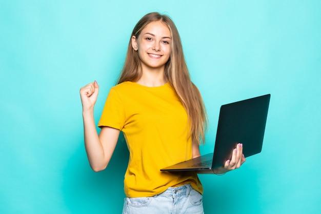 청록색 벽에 고립 된 포즈 승리 제스처와 노트북에서 일하는 젊은 여자