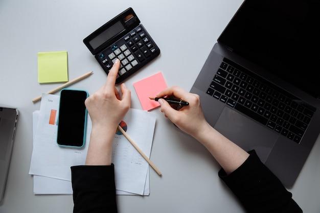 オフィスの机、上面図で働く若い女性。ノートパソコンと電卓を使って、何かアイデアをメモします