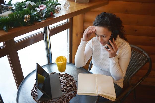カフェでオンラインで働いて、携帯電話で話し、テーブルの上のタブレットを見ている若い女性