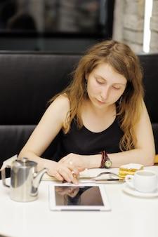若い女性が働くか、カフェで彼女のタブレットコンピューターで勉強 Premium写真